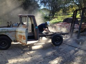 Jim Tronier getting to work sandblasting the 1956 Chevrolet truck frame.